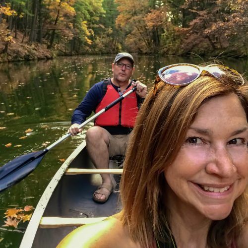 Middle aged couple kayaking in autumn